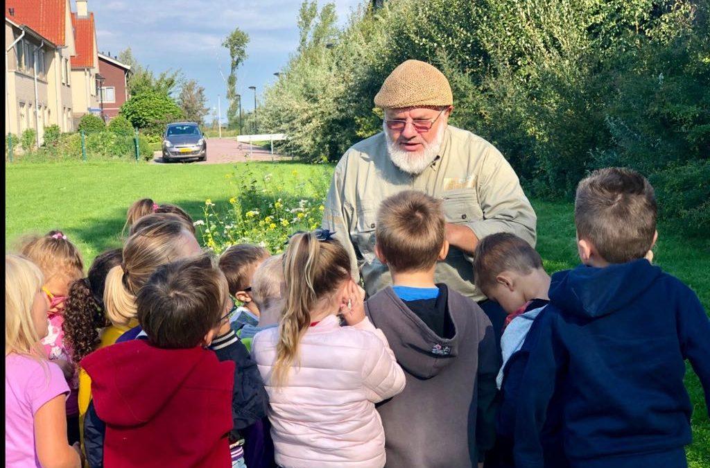 Imker leert kinderen over vriendschap tussen bloem en insect